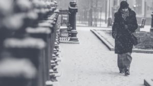 Solitary person walking on a snow filled sidewalk.